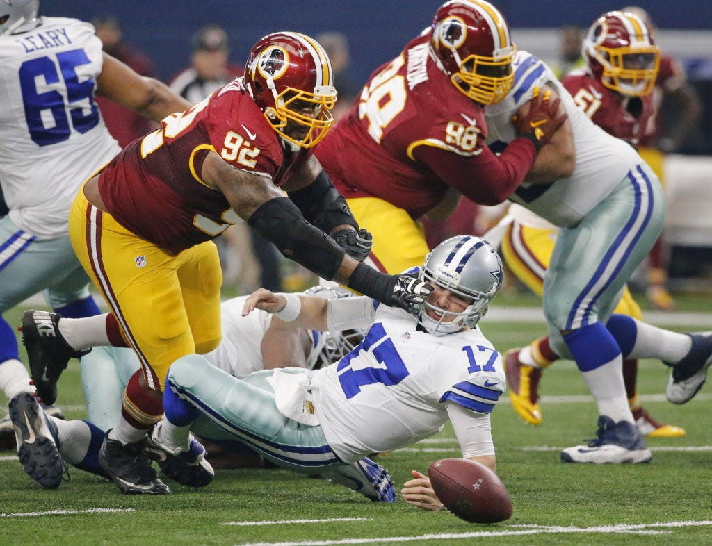 Washington Redskins defensive end Chris Baker (92) mows over Dallas Cowboys quarterback Kellen Moore (17) to recover a fumble after Moore fumbled the snap in the first quarter during the Washington Redskins vs. the Dallas Cowboys NFL football game at AT&T Stadium in Arlington on Sunday, January 3, 2016. (Louis DeLuca/The Dallas Morning News)
